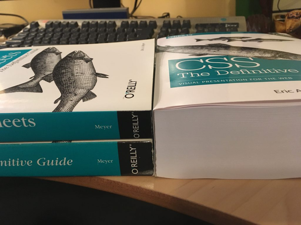 """The fourth edition of """"CSS: The Definitive Guide"""" sits on a desk to the right. To the left are the second and third editions of the same book, one atop the other. The two stacked books are, together, almost exactly the same height as the single book on the right."""