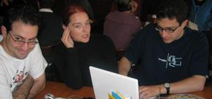 Derek Powazek, Heather Champ, and Tantek �elik are seated at a table.  Derek is looking off to the left with an expression of diabolical amusement; Heather is speaking to someone outside the frame, her right hand to her cheek; and Tantek types away on his new Macintosh iBook.