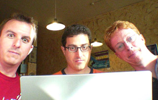 A picture of Doug, Tantek, and Eric peering over the display panel of Tantek's TiBook.