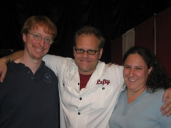 A photograph of Alton Brown with his arms around Eric and Kat.