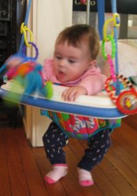 Carolyn happily jumps about in her 'bouncy seat', a chair suspended from a door frame and incorporating a spring so that she can bounce up and down even though she hasn't the coordination to stand yet.