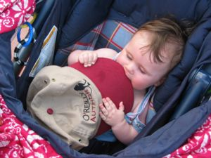 "A photograph of six-month-old Carolyn chewing on the rim of her father's ""O'Reilly Author"" baseball cap."