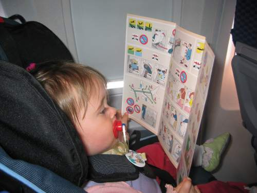 Carolyn, strapped into her seat on the plane, solemnly looks over the airline safety information card.