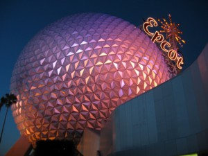 A photograph of the Spaceship Earth globe, illuminated by purple and pink lights in the deep twilight of a Florida evening.