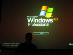 Tantek Çelik stands silhouetted in front of a projection screen on which can be seen a giant Windows XP bootup screen.