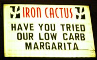 "A lighted sign that reads ""HAVE YOU TRIED OUR LOW CARB MARGARITA"""