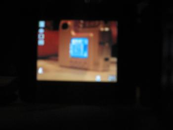 A blurry image of the display panel of another digital camera, which shows that camera is pointed at the display panel of yet another digital camera.