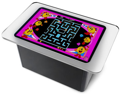 A picture of a Microsoft Surface unit with Ms. Pac-Man Photoshopped onto the display area, thus recalling the tabletop Ms. Pac-Man arcade games of yore.